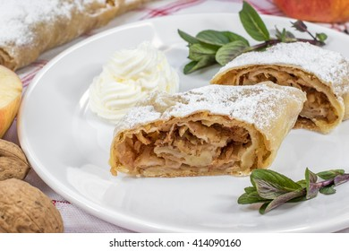Detail on One Slice Homemade Apple Strudel on a Plate with Whipped Cream and Mint