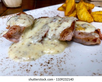 detail on pork tenderloin in cheese sauce sliced and served with deluxe french fries