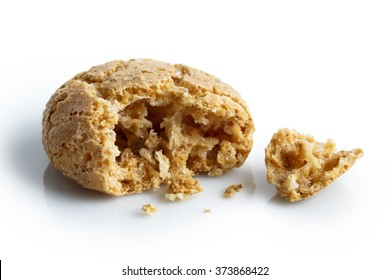 Detail of one broken Italian amaretti biscuit isolated on white in perspective, with crumbs.