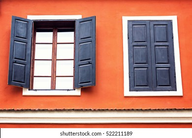 Detail of an open wooden iron vintage rustic windows on red cement old wall can be used for background. Brown black window shutters with decorative flowers