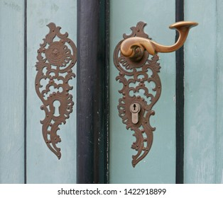 Detail of ornate vintage door handle on a pale green wooden door
