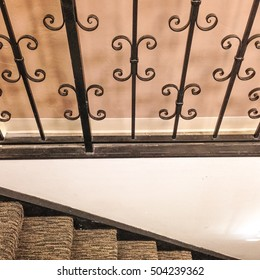 Detail of outdated carpeted stairs and wrought iron railing