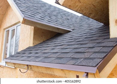 Detail of overlapping roofing tiles on a new build wooden house with dormer windows