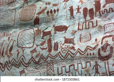 """Detail of the paintings on a rock in """"Cerro Azul"""" in La Lindosa, Guaviare. Primitive art on red pigments over a white natural rock, paintings of animals an tribal patterns. Near Chiribiquete formation"""