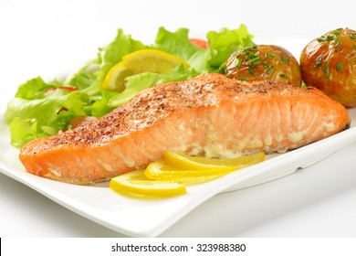 detail of pan fried salmon fillet served with roasted potatoes and fresh vegetables on white square plate