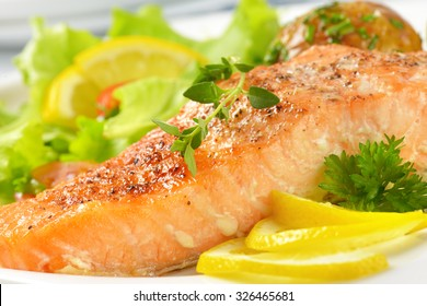 detail of pan fried salmon fillet served with fresh vegetables