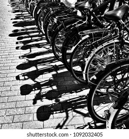 Detail of parked bikes with shadows on the pavement in Amsterdam