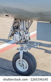 Detail part of wheel and brake system of  fighter jet military aircraft parked on the ground in runway