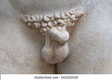 Detail of a partially damaged antique Greek marble sculpture. Adult male groin with testicles, penis and pubic hair.