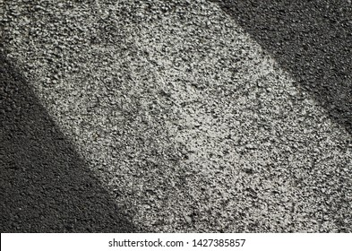 Detail of a pedestrian strip on the asphalt, damaged by time. - Shutterstock ID 1427385857