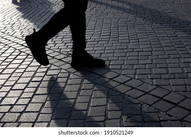 Detail of people rushing over the pavement at a train station during rush hour with sun coming from the side and long shadows