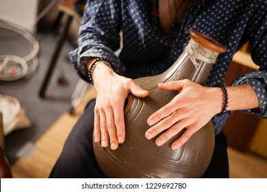 Detail of a percussionist hands while playing udu instrument on a rehearsal studio. Metal percussion exotic flamenco instruments concept.