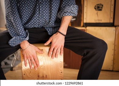 Detail of a percussionist hands while playing flamenco drumbox on a rehearsal studio with more drum boxes on the background. Flamenco instruments and musicology concept.