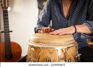 Detail of a percussionist hands while playing congas instrument on a rehearsal studio with spanish guitar on the background. Membranophones percussion flamenco instruments concept. Musicology concept.
