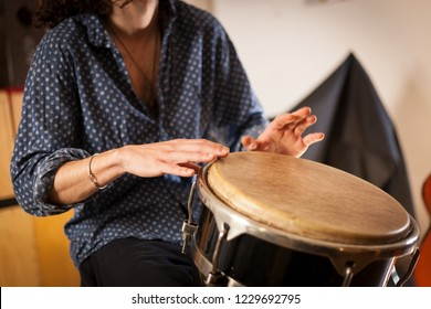 Detail of a percussionist male hands while playing bongos on a rehearsal studio with natural light. Percussion instruments and musicology concept.