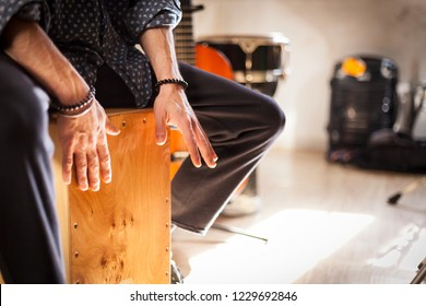 Detail of a percussionist male hands while playing flamenco drumbox on a rehearsal studio with drums and music stuff on the background with natural light. Flamenco instruments and musicology concept.