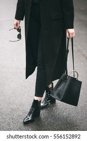 detail of a perfect fall fashion outfit. fashionable woman wearing a black oversized coat, black jeans, black ankle shoes a black trendy handbag. fashion blogger outfit details.