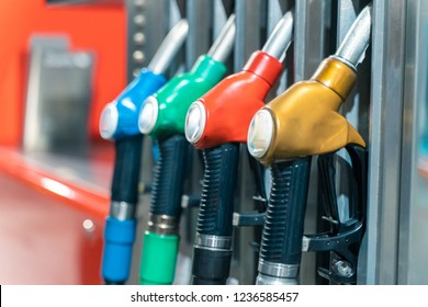 Detail of a petrol pump in a petrol station.Close up on fuel nozzle in oil dispenser with gasoline and diesel in service gas station. Pattern petrol pump gun filling. Blue, green, red, golden colors.