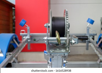 detail photo of the mechanical rope winch with hook on the trailer for towing small boats