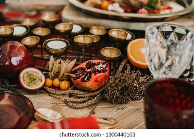 Detail photograph of a table prepared and decorated for a party diner. Autumnal and festive decoration, with wood pineapples, candles, fruits and red colors. Lifestyle. Food photography