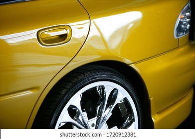 Detail photography of a yellow car on display at an auto show