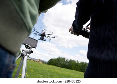 Detail of pilot and photographer operating a UAV drone with SLR camera