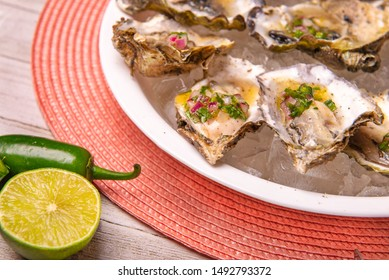 Detail of a plate with fresh shucked oysters with jalapeno & lemon mignonette over wood background