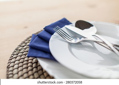 detail of plates and cutlery on wooden table