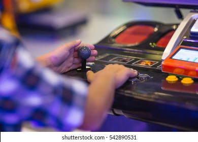Detail of player hand interacting and playing with joysticks and buttons on an old arcade game in a gaming room