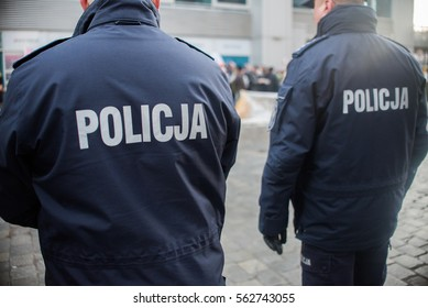 detail of a police (Policja) officer in Poland, demonstration in background