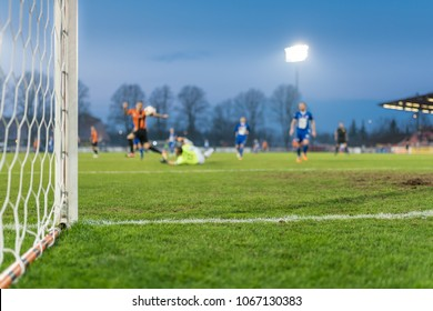 Detail of the post and net of the football goal in the background players in action.