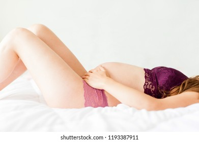 Detail Of Pregnant Belly Of Young And Beautiful Woman Laying On Bed