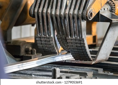Detail of a puller pulling an aluminium profile on an extrusion profile roller runout table.