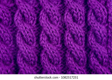 Detail of purple handknit coiled rope cable knitting stitch