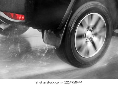 Detail of the rear wheel of a car driving in the rain on a wet road. Aquaplaning in road traffic.