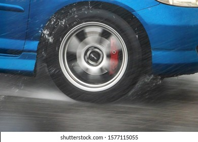A Detail of the rear wheel of a car driving in the rain on a wet road. Aquaplaning in road traffic.