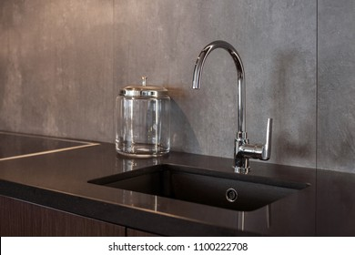 Detail of a rectangular designer kitchen sink with chrome water tap against a gray textured wall