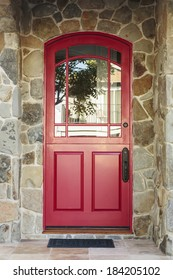 Detail of a red front door to a home in daytime. The door is arched with glass windows, and is framed by the house's stone detail. Also seen is greenery, a doormat, and the reflection of a tree.