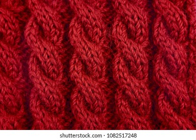 Detail of red handknit coiled rope cable knitting stitch