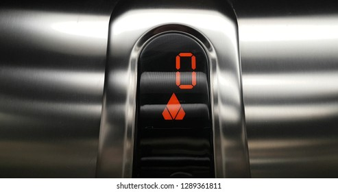 detail of red led with number zero of elevator that go up from zero to first floor, business and technology  concept