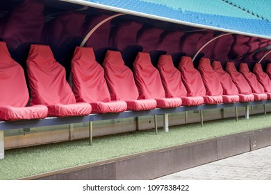 Detail of red Reserve chair and staff coach bench in sport stadium