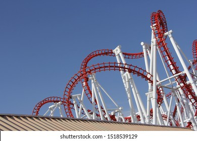 detail of red roller coaster big dipper track on huge white steel support legs and blue sky