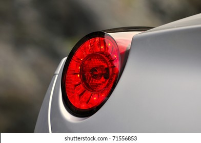 detail of red tail light on a silver car
