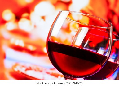 detail of red wine glasses against unfocused restaurant table background, festive and fun concept