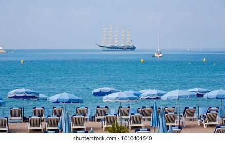 detail of a relaxing area in a beach in Cannes, in the famous French Riviera, facing the Mediterranean sea, with some comfortable sunloungers and some colorful umbrellas