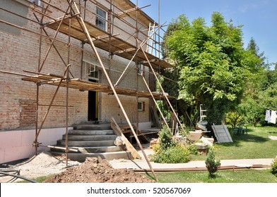 detail renovation of house with scaffold and nice garden with tree and blue sky. Reconstruction of building