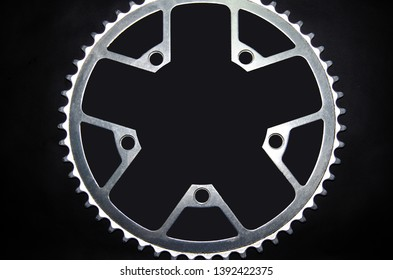 Detail for a road bike on a black background. Old school crankset and chainrings close-up. Soft side light with a slight yellow tint. Bicycle repair.