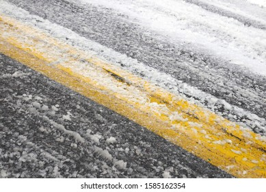 Detail of road with snow slush and yellow line