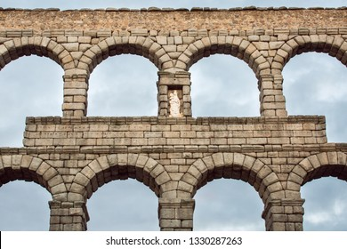 Detail of roman aqueduct, Virgin of the Aqueduct, located in the central niche of the monument has since the Plaza del Azoguejo, Segovia, Spain - Image