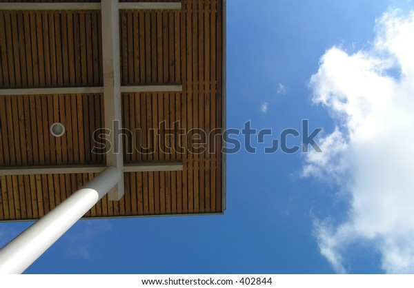 Detail of roof against blue sky with clouds